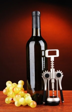 Composition of corkscrew and bottle of wine, grape, on wooden table on dark background photo