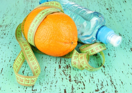 Orange with measuring tape, bottle of water, on  color wooden background photo