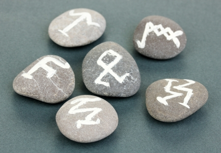 Fortune telling  with symbols on stones on grey background Stock Photo - 19300062