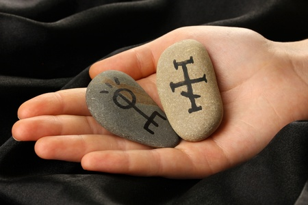 Fortune telling  with symbols on stone in hand on black fabric background Stock Photo - 19279025