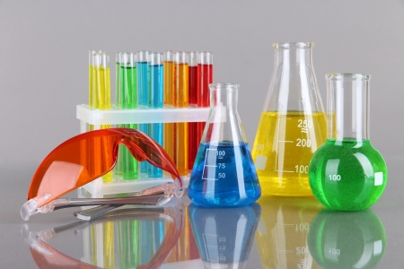 Test-tubes with colorful liquids on gray background photo