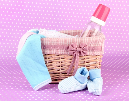 Beautiful basket of baby clothes on a pink background photo