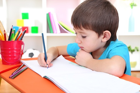 assiduous: Cute little boy drawing in his album Stock Photo