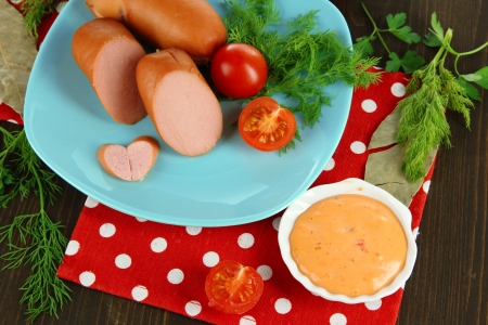 Sausage, greens, tomato on plate on wooden table photo
