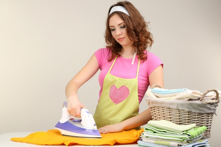 domesticity: Young beautiful woman ironing clothes in room on grey background