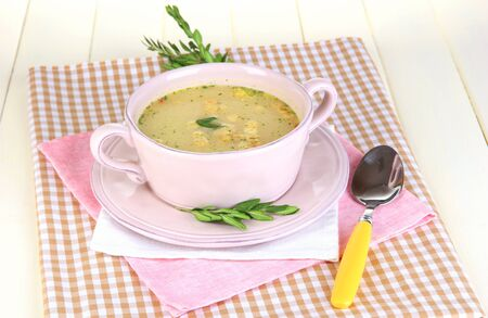 nourishing: Nourishing soup in pink pan on wooden table close-up