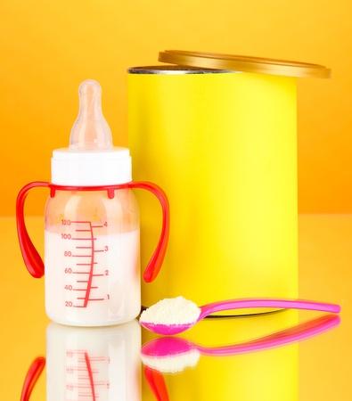 fondo para bebe: Botella con la leche y los alimentos para beb�s en el fondo de color naranja