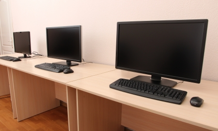 Computers on tables in room Stock Photo