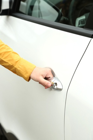 Woman hand opening car door, close up photo