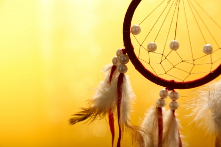 Beautiful dream catcher on yellow background photo