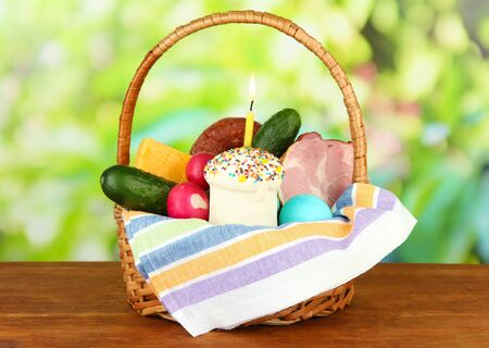 Easter basket: Conceptual photo of traditional easter food in wicker basket, on wooden table on bright background photo