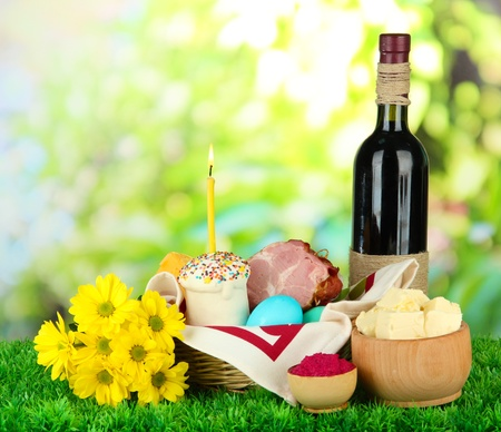 Easter basket: Conceptual photo of traditional easter food in wicker basket, on green grass, on bright background photo