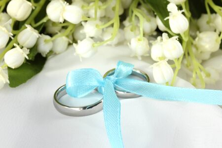 wedlock: Wedding rings tied with ribbon on light gentle background Stock Photo