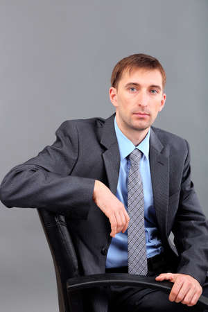 careerists: Young businessman  on grey background