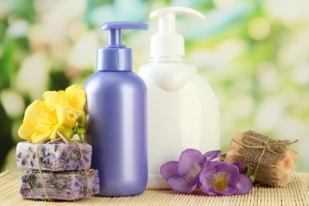liquid soap: Liquid and hand-made soaps on wooden table, on green background