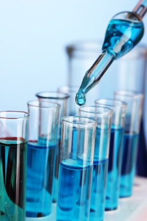 Pharmaceutical research: Laboratory pipette with drop of color liquid over glass test tubes, close up Stock Photo