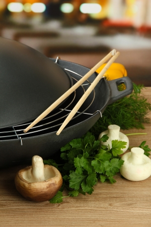 cooking utensils: Black wok pan and vegetables on kitchen wooden table, close up