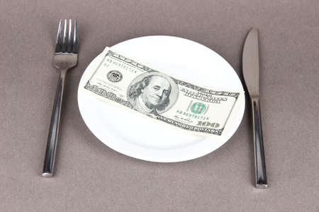 food inspection: Money on plate on grey background Stock Photo