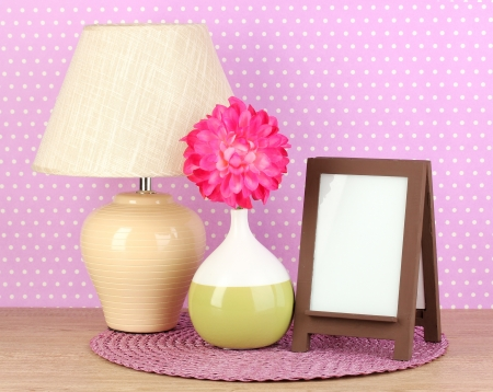lamp stand: Brown photo frame and lamp on wooden table on lilac wall background