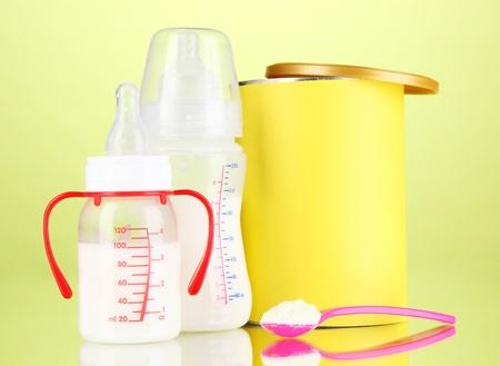 fondo para bebe: Botellas con leche y alimentos para beb�s en fondo verde Foto de archivo