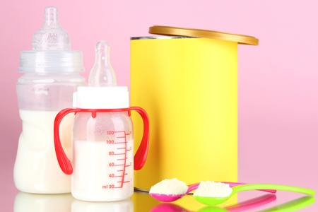 Bottles with milk and food for babies on pink background photo