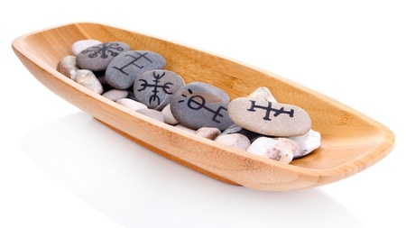 Fortune telling  with symbols on stones in wooden bowl isolated on white photo