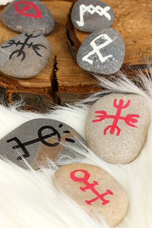 Fortune telling  with symbols on stones on white fur background photo