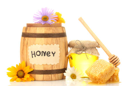 Sweet honey in jar and barrel with honeycomb, wooden drizzler and flowers isolated on white photo