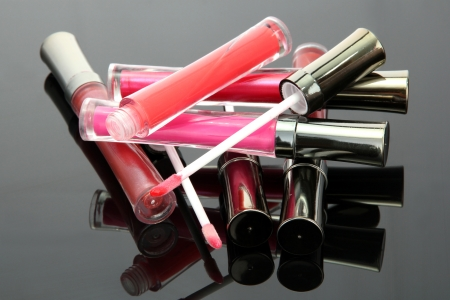 lip gloss: beautiful lip glosses with rose petals, on grey background