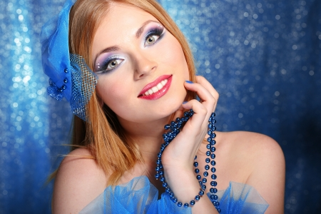 Portrait of beautiful young woman with glamour make up, on blue background photo