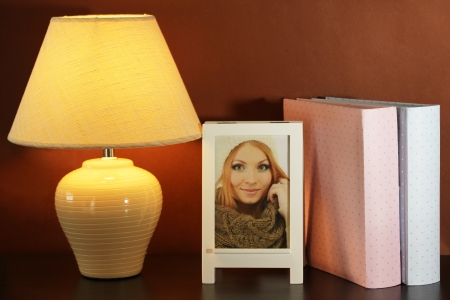 White photo frame and lamp on wooden table on brown wall background photo