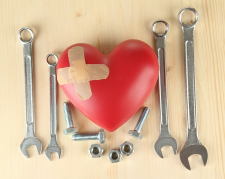 Heart and tools. Concept: Renovation of heart. On wooden background photo