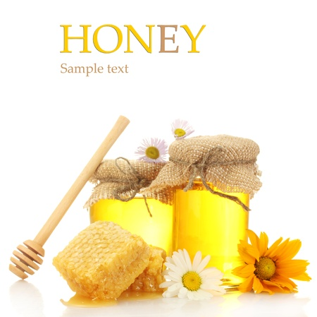 Jars of honey and honeycombs isolated on white photo