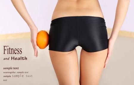 muslos: Hermosa figura femenina con la naranja sobre fondo claro