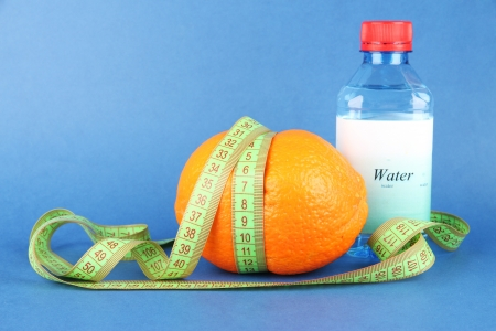 Orange with measuring tape, bottle of water, on color background photo