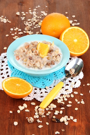 eat right: Useful oatmeal in bowl with fruit on wooden table close-up Stock Photo