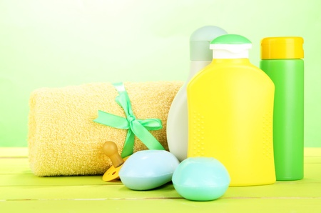 Baby cosmetics, soap and towel on wooden table, on green background photo