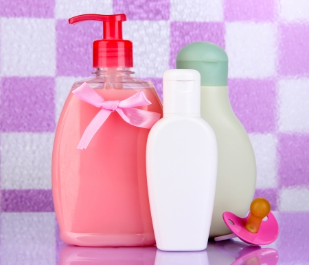 Baby cosmetics in bathroom on violet tile wall background photo