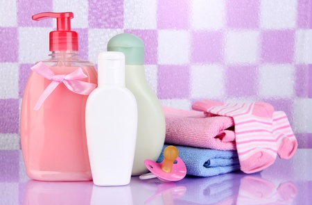 Baby cosmetics and towels  in bathroom on violet tile wall background Stock Photo - 19514751