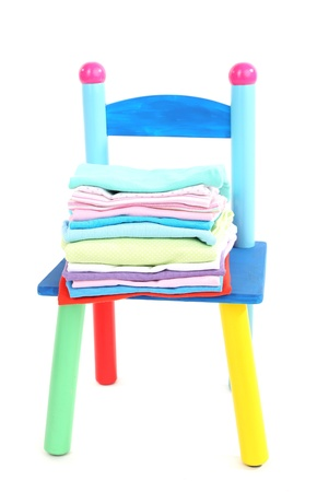 Small and colorful chair with baby clothes isolated on white Stock Photo - 19510732