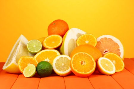 Lots ripe citrus on wooden table on orange background photo