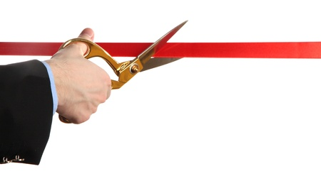 unveiling: Mans hand cutting red ribbon with pair of scissors isolated on white Stock Photo