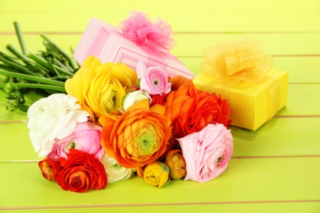 persian green: Ranunculus (persian buttercups) and gifts, on green wooden background Stock Photo