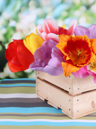 Beautiful tulips in bouquet in wooden box on table on bright background photo