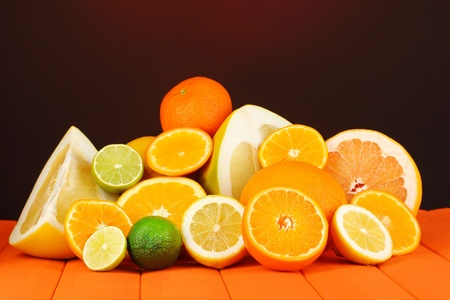 Lots ripe citrus on wooden table on dark color background photo