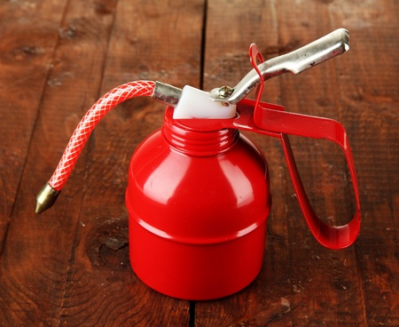Red oil can, on wooden background Stock Photo - 19650311