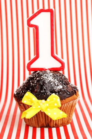 Birthday cupcake with chocolate frosting on striped background photo