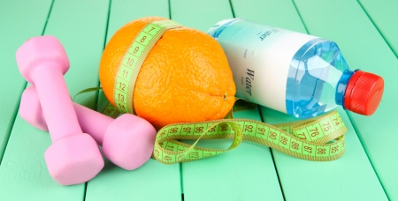 Orange with measuring tape, dumbbells and bottle of water, on color wooden background photo