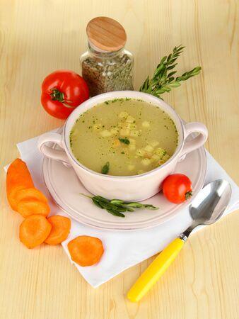 nourishing: Sopa nutritiva en el molde rosa con los ingredientes sobre la mesa de madera en primer plano