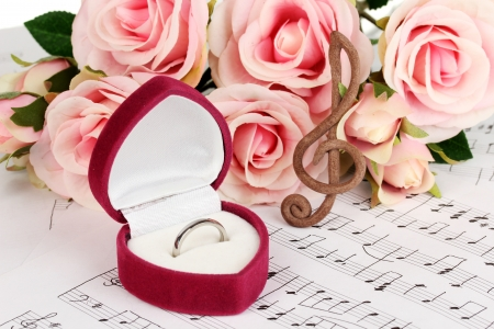 Treble clef, roses and box holding wedding ring on musical background photo
